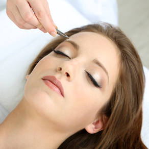 Beautiful woman receiving a relaxing waxing treatment for eye brows.
